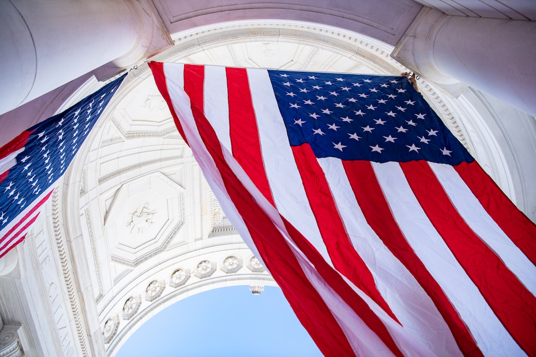 American flags hang from an ornate white archway.