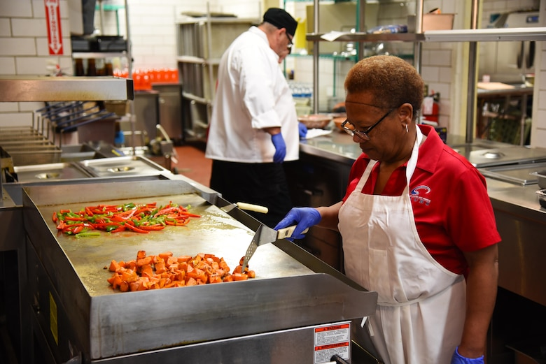 Mary Johnson, a cook at the Columbus Club, cooks and prepares food on a flattop grill Nov. 4, 2019, on Columbus Air Force Base, Miss. To provide different people with different tastes the Club is providing more options like vegetarian and vegan meals with fresh vegetables as well as more dishes with white meat in them. (U.S. Air Force photo by Airmen 1st Class Jake Jacobsen)