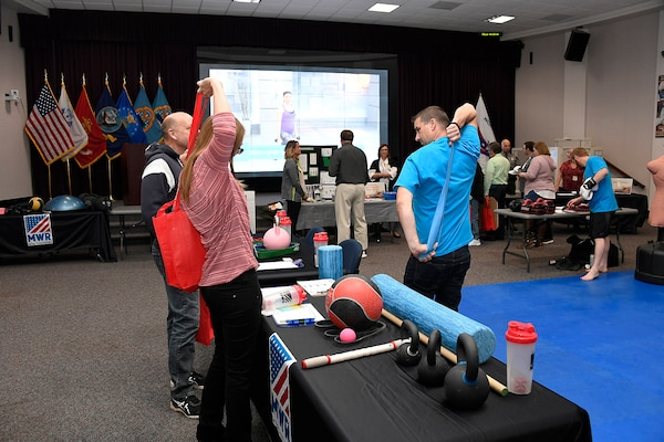 MWR Personal Trainer Daniel Roberts demonstrates uses for elastic bands on display with training equipment.