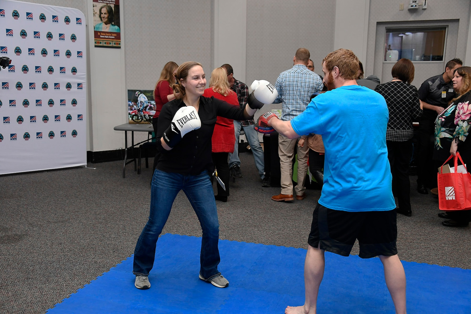 Kristy Hardin (left) throws some training punches with MWR Personal Trainer Chisholm.