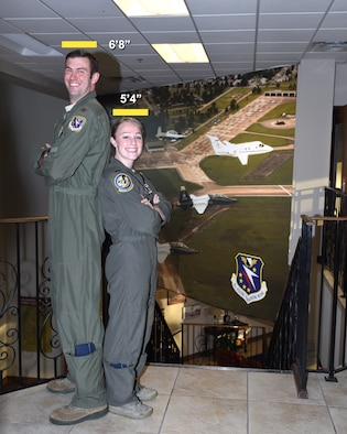 Maj. Nate and 1st Lt. Christina Nicholson, 48th Flying Training Squadron instructor pilot, stand next to each other to show their height difference Oct. 30, 2019, on Columbus Air Force Base, Miss. The standing height requirements to become a pilot are a minimum 5 feet 4 inches and maximum 6 feet 5 inches, but can be dismissed through the waiver process. (U.S. Air Force photo by Sharon Ybarra)