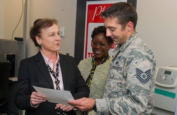 Erin O'Brien, National Air and Space Intelligence Center director of personnel, presents a certificate of recognition to Tech Sgt. Matthew Paine, Education and Training noncommissioned officer in charge, for his efforts in the face of adversity. On Paine's drive home from work, Oct. 24, 2019 he noticed that an elder was in need of help, Paine he stopped to help a local citizen in need of help. (Photo by Tech. Sgt Benjamin Wiseman)