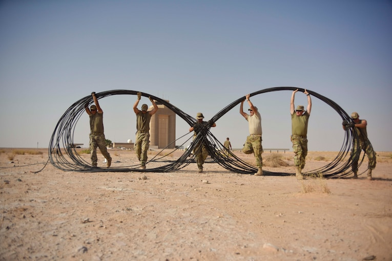 A group of airman move a cable.