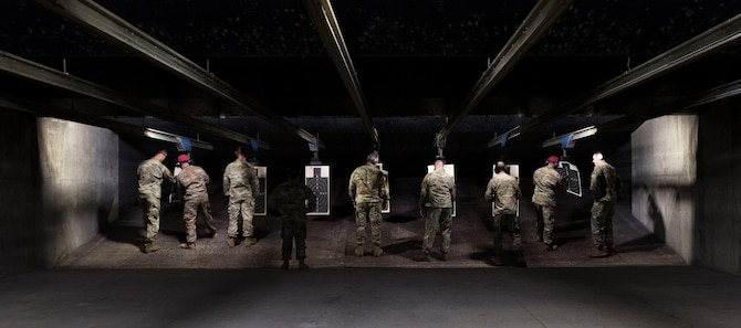 U.S. Air Force combat arms instructors and participants look over practice targets at an inaugural M9 pistol Excellence in Competition shooting event at the Combat Arms range complex at Shaw Air Force Base, South Carolina, Nov. 6, 2019.