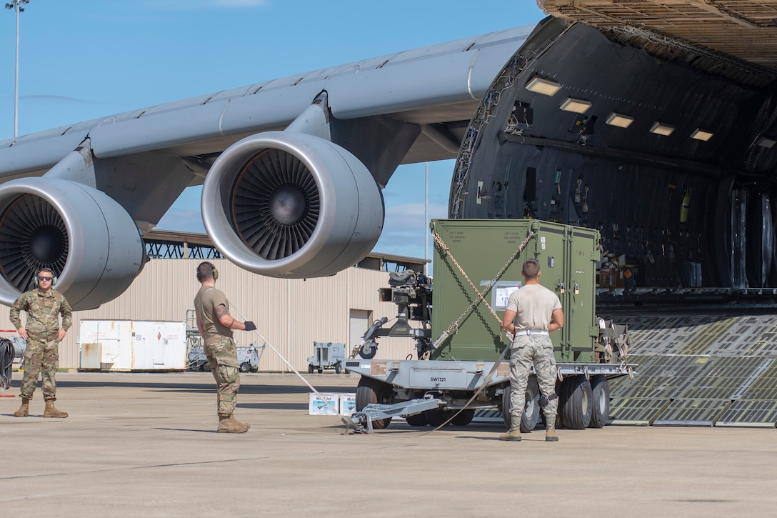 From left, U.S. Air Force Airman 1st Class Michael Shelton, 9th Airlift Squadron loadmaster, Senior Airman Jacob Guy, 20th Logistics Readiness Squadron (LRS) small air terminal deployment instructor, and Airman 1st Class Justen McCallister, 20th LRS aerial transportation specialist, wait to begin loading cargo aboard a C-5M Galaxy on the flightline at Shaw Air Force Base, South Carolina, Oct. 24, 2019.