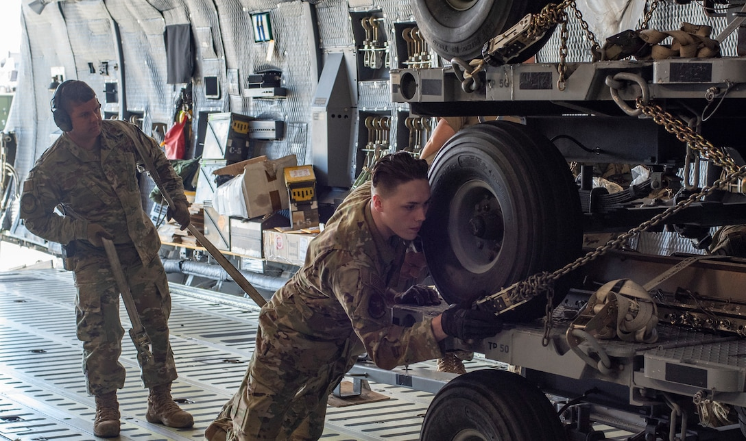 From left, U.S. Air Force Tech. Sgt. William Young, a 20th Logistics Readiness Squadron aerial transportation specialist, and Senior Airman Brandon Driver, 9th Airlift Squadron loadmaster, load cargo onto a C-5M Super Galaxy, at Shaw Air Force Base, South Carolina, Oct. 24, 2019.