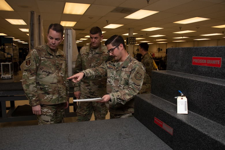 U.S. Air Force Staff Sgt. Vincenzo Kopilow, 60th Maintenance Squadron physical dimensional craftsman, right, briefs Col. Jeff Nelson, left, 60th Air Mobility Wing commander, and Chief Master Sgt. Derek Crowder, center, 60th AMW command chief, about the capabilities of an electromagnetic height gauge during a Leadership Rounds visit Nov. 1, 2019 at Travis Air Force Base, California. The Precision Measurement Equipment Laboratory at Travis, where Kopilow works, is responsible for a ensuring the accuracy of test equipment for 255 work centers. The Leadership Rounds program provides 60th AMW leadership an opportunity to interact with Airmen to get a detailed view of each mission performed at Travis AFB. (U.S. Air Force photo by Tech. Sgt. James Hodgman)