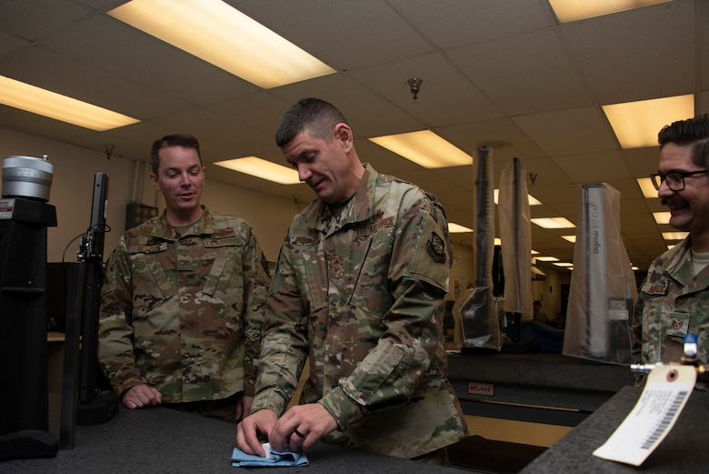 U.S. Air Force Chief Master Sgt. Derek Crowder, center, 60th Air Mobility Wing command chief, works with gauge blocks during a Leadership Rounds visit inside the 60th Maintenance Squadron Precision Measurement Equipment Laboratory while Col. Jeff Nelson, left, 60th AMW commander and Staff Sgt. Vincenzo Kupilow, right, 60th MXS physical dimensional craftsman, look on Nov. 1, 2019 at Travis Air Force Base, California. The PMEL team is responsible for ensuring the accuracy of test equipment for 255 work centers. The Leadership Rounds program provides 60th AMW leadership an opportunity to interact with Airmen to get a detailed view of each mission performed at Travis AFB. (U.S. Air Force photo by Tech. Sgt. James Hodgman)