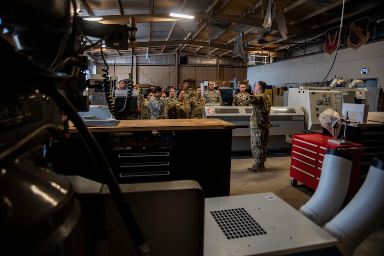 First lieutenant Matthew Gill, 53rd Test Support Squadron special devices engineering section chief, facilitates an immersion tour at the special devices flight metal fabrication shop for members assigned to the 325th Fighter Wing on Nov. 8, 2019, at Tyndall Air Force Base, Florida. Airmen visited multiple units of the 53rd Weapons Evaluation Group during the tour. The group was also participating in the Weapons System Evaluation Program and Checkered Flag 20-1 exercise on Tyndall's flight line. Attendees also learned about the unit's joint partnership with Tyndall, ensuring Airmen are trained and equipment is tested, to support the warfighter. (U.S. Air Force photo by Staff Sgt. Magen M. Reeves)