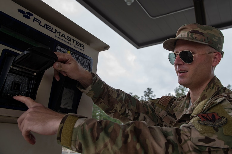 A photo of an Airman checking a vehicle interface link socket on a fuel service station