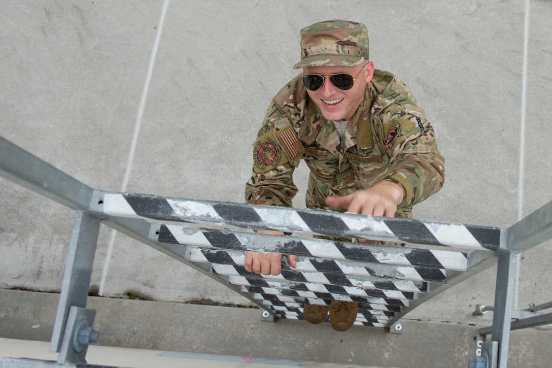 A photo of an Airman climbing a ladder on a fuel tank
