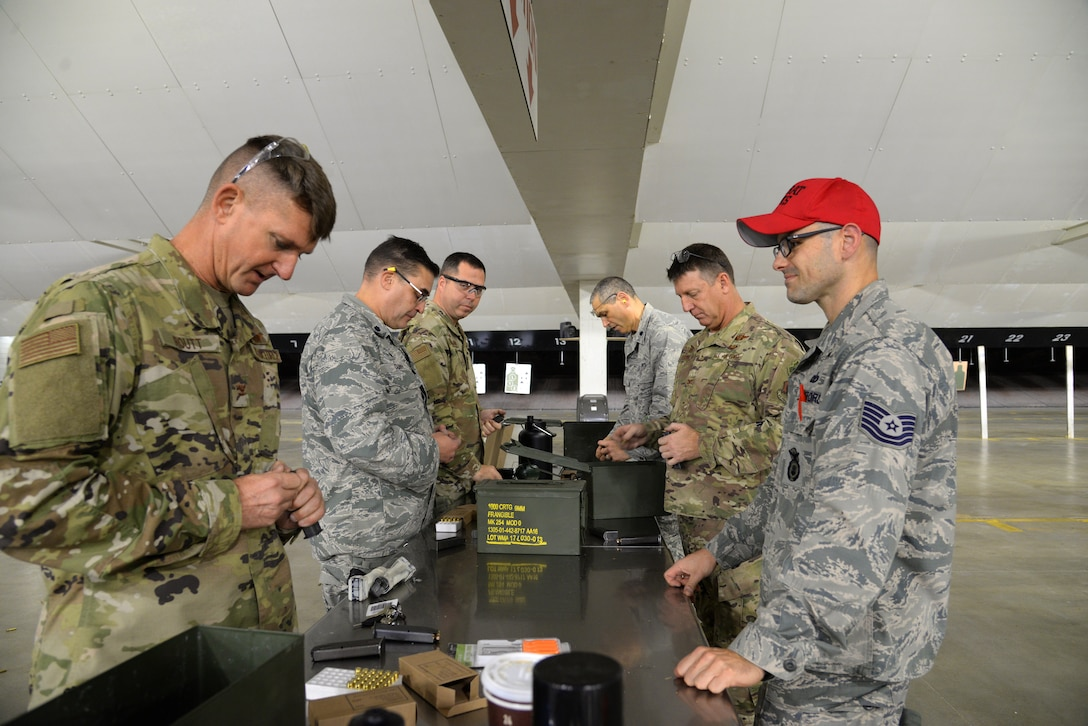 A picture of Sgt. Jason Cullen, 177th Fighter Wing Security Forces Squadron combat arms non-commissioned officer in charge, watching the wing commander and group commanders of the 177th Fighter Wing load 9 millimeter magazines at a firing range.
