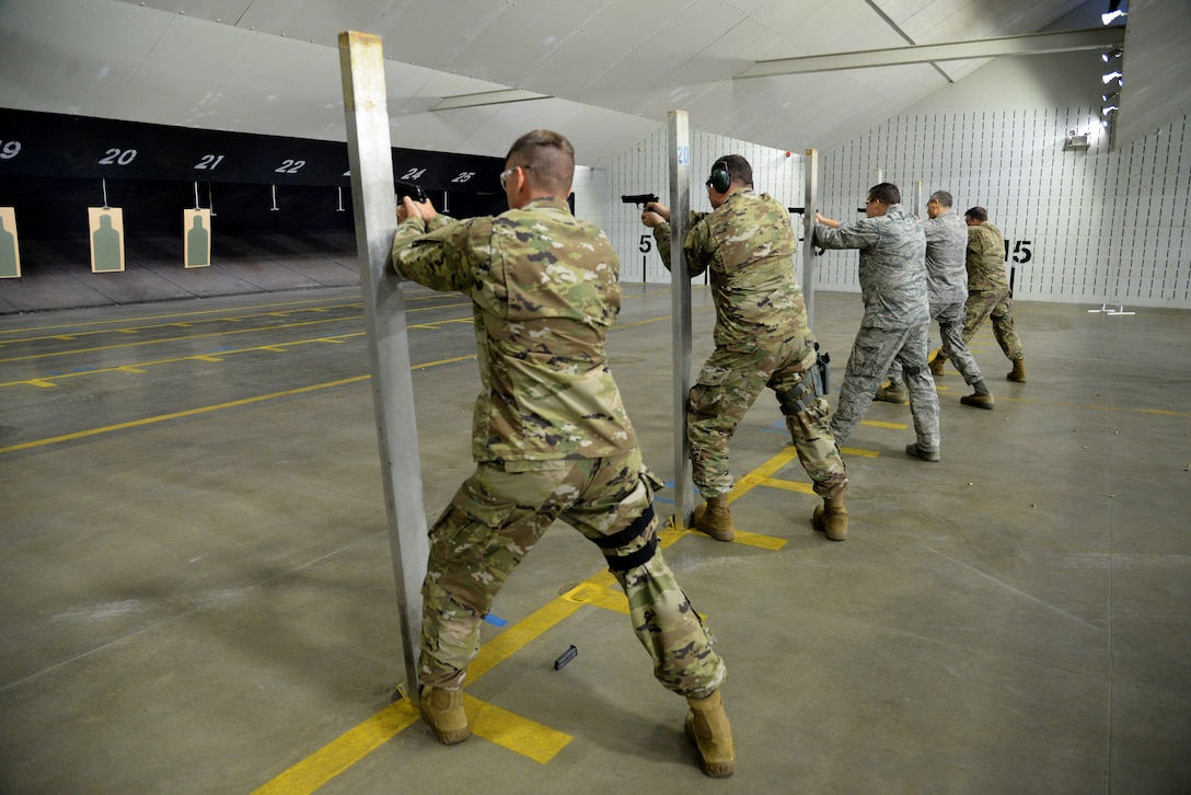 A picture of the wing commander and group commanders of the 177th Fighter Wing firing the M9 pistol at a firing range.