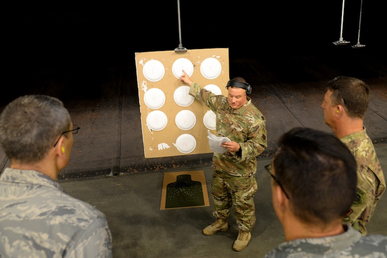 A picture of U.S. Air Force Staff Sgt. Dylan Manno, 177th Fighter Wing Security Forces Squadron combat arms trainee, points at paper targets at a firing range.