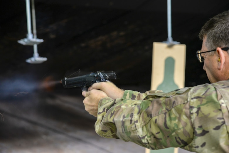 A picture of U.S. Air Force Colonel Bradford Everman, 177th Fighter Wing commander, firing the M9 pistol at a firing range.
