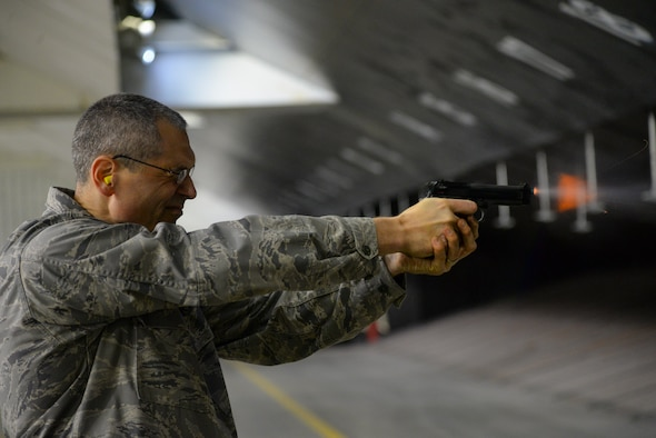 A picture of U.S. Air Force Lieutenant Colonel Eric Erickson, 177th Medical Group commander, firing the M9 pistol at a firing range.
