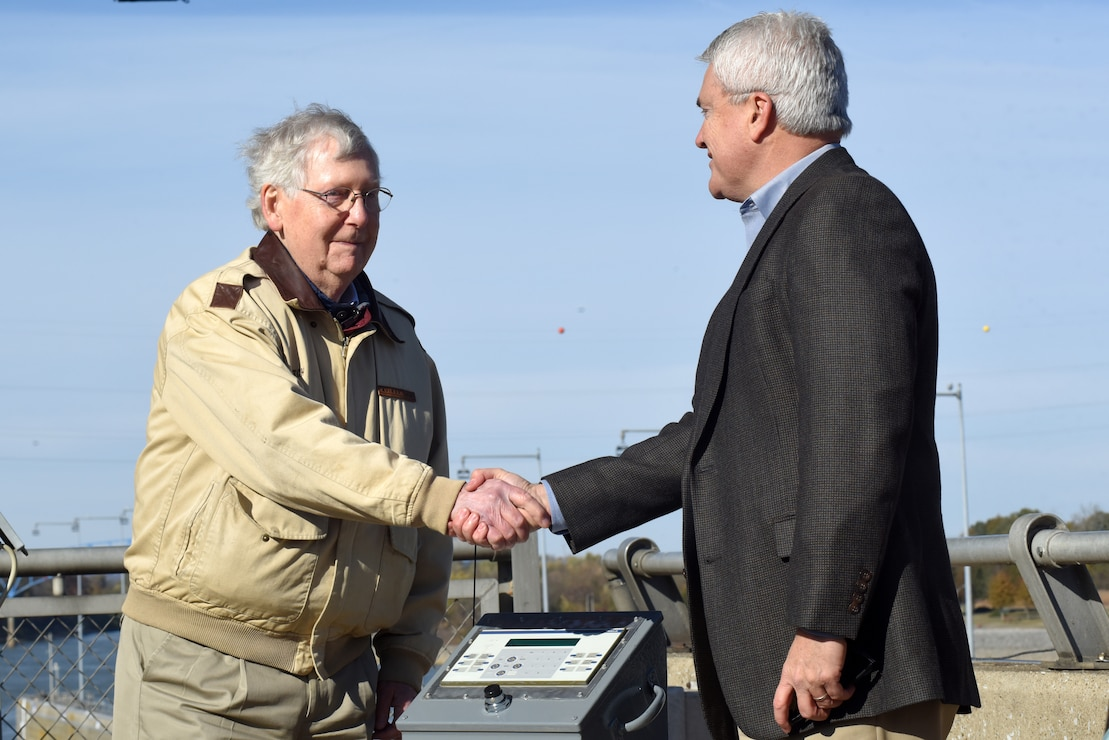 Senate Majority Leader Mitch McConnell (Left) and Congressman James Comer, Kentucky 1st District, congratulate each other after McConnell initiated a button to commission a bio-acoustic fish fence Nov. 8, 2019 below Barkley Lock in Grand Rivers, Ky. The BAFF sends a curtain of bubbles, sound and light from the riverbed to the water surface, which deters noise-sensitive Asian carp from entering the lock chamber. Fisheries managers on the west coast of the United States use a similar system to guide the movement of trout and salmon from water channels. This marks the first time a BAFF has been tested at a lock and dam on a large river. Construction of the BAFF began in July 2019. The project involves multiple partners, including U.S. Fish and Wildlife Service, Kentucky Department of Fish and Wildlife Resources, U.S. Army Corps of Engineers Nashville District, U.S. Geological Survey, and Tennessee Wildlife Resources Agency. Fish Guidance Systems, a United Kingdom-based company specializing in fish deflection and guidance systems, provided the BAFF technology at Barkley Lock.  (USACE photo by Lee Roberts)