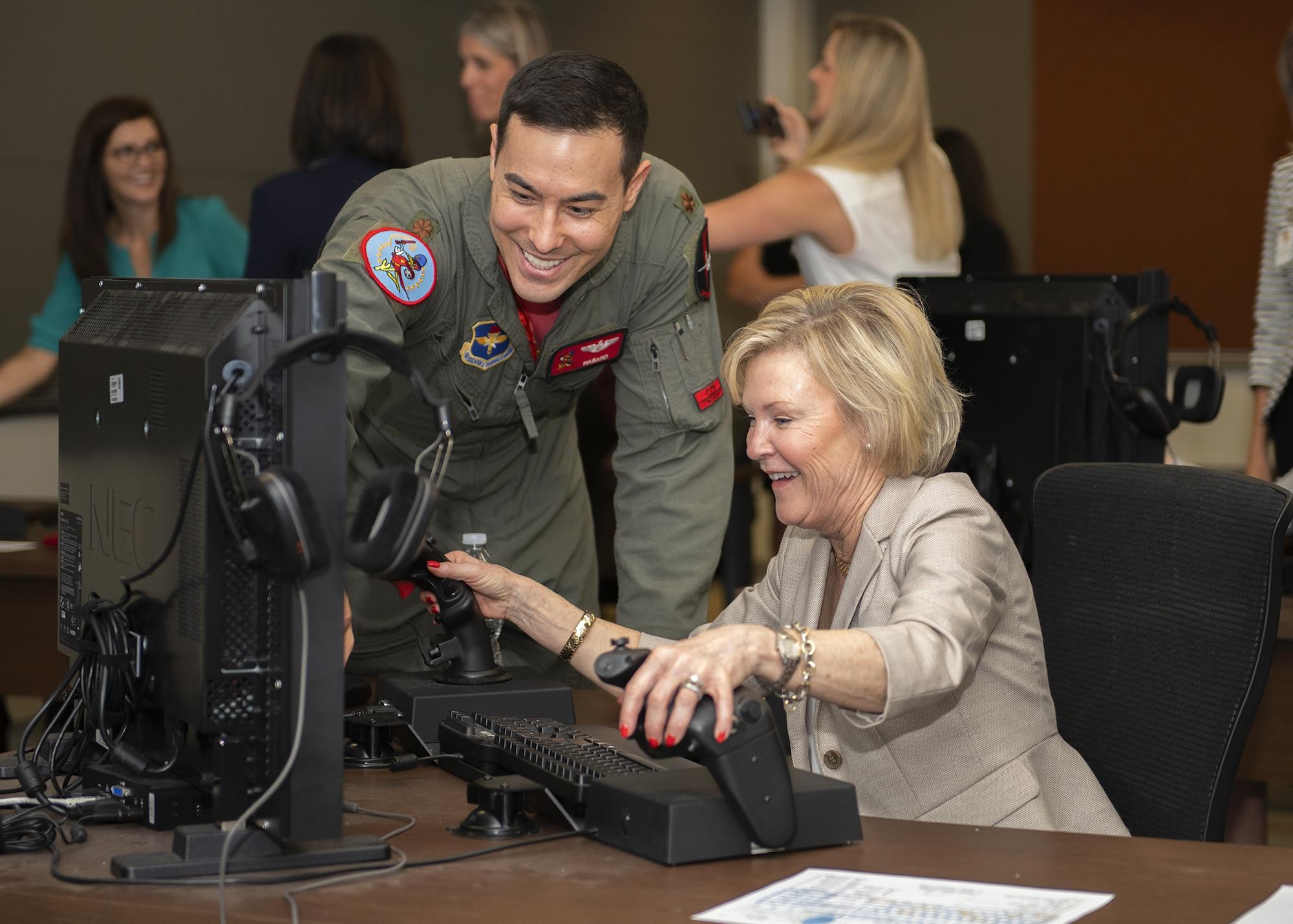 Maj. Justin Lee, 56th Training Squadron instructor pilot, shows Dawn Goldfien, wife of Air Force Chief of Staff Gen. David L. Goldfein, how to operate an F-35A Lightning II simulator at Luke Air Force Base, Ariz., Nov. 8, 2019.