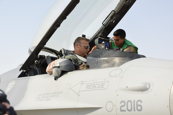 A U.S. Air Force crew chief assists U.S. Air Force Lt. Gen. Joseph Guastella, commander of U.S. Air Forces Central Command, before his flight in an F-16 Fighting Falcon at Al Udeid Air Base, Qatar Nov. 4, 2019.