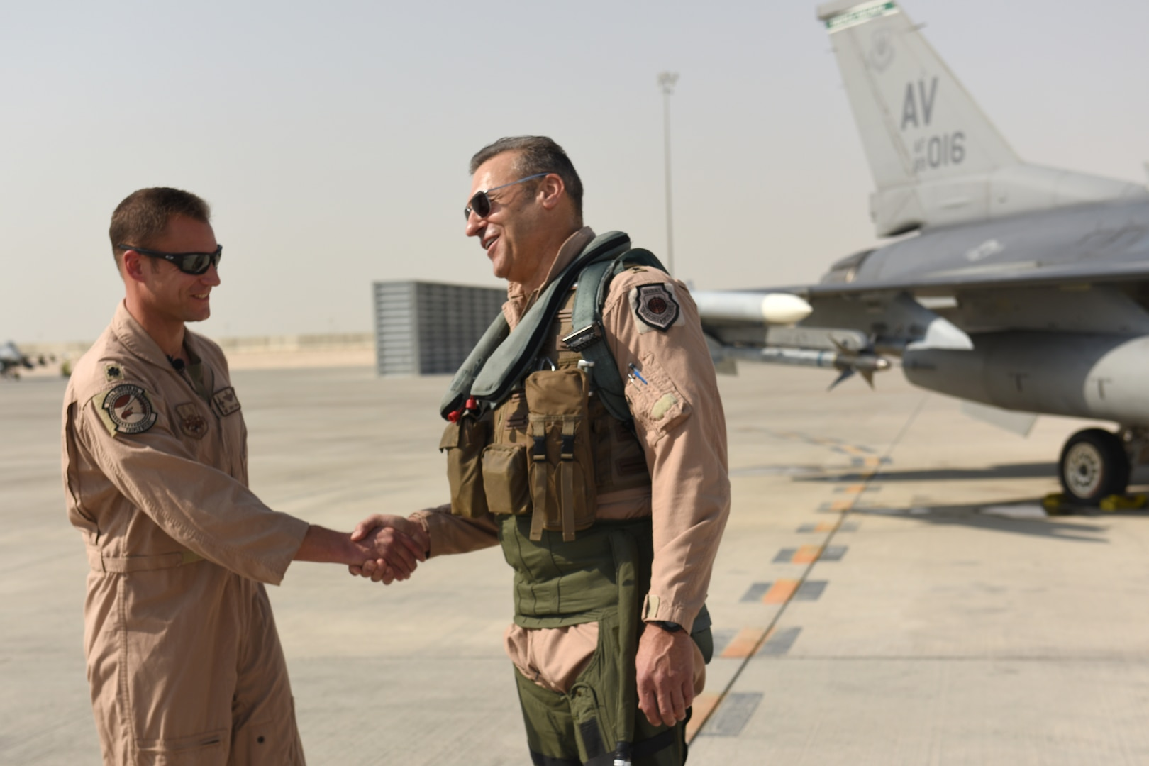 U.S. Air Force Lt. Col. Beau Diers, commander of the 555th Fighter Squadron, shakes hands with USAF Lt. Gen. Joseph Guastella, commander of U.S. Air Forces Central Command, before the general's flight in an F-16 Fighting Falcon at Al Udeid Air Base, Qatar Nov. 4, 2019.