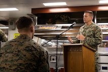 the commanding officer of the 11th Marine Expeditionary Unit speaks to Marines and Sailors during a 244th Marine Corps birthday celebration