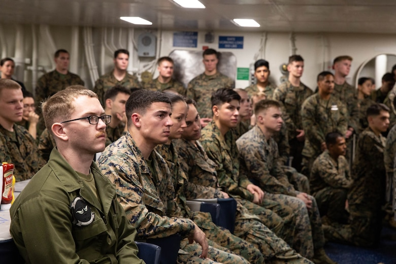 Marines and Sailors observe a speaker during a 244th Marine Corps birthday celebration