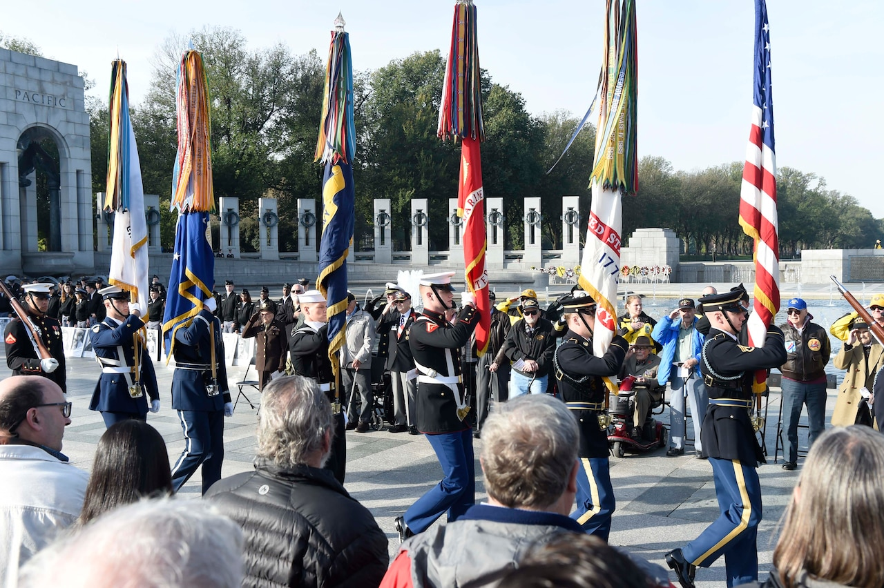 Color guard marches in formation as people salute