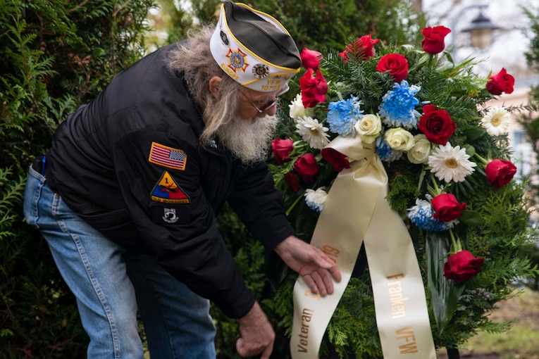 A man places a wreath on a stand.