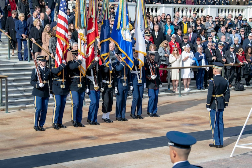 A group of service members stand in a line in front of a crowd, holding flags.