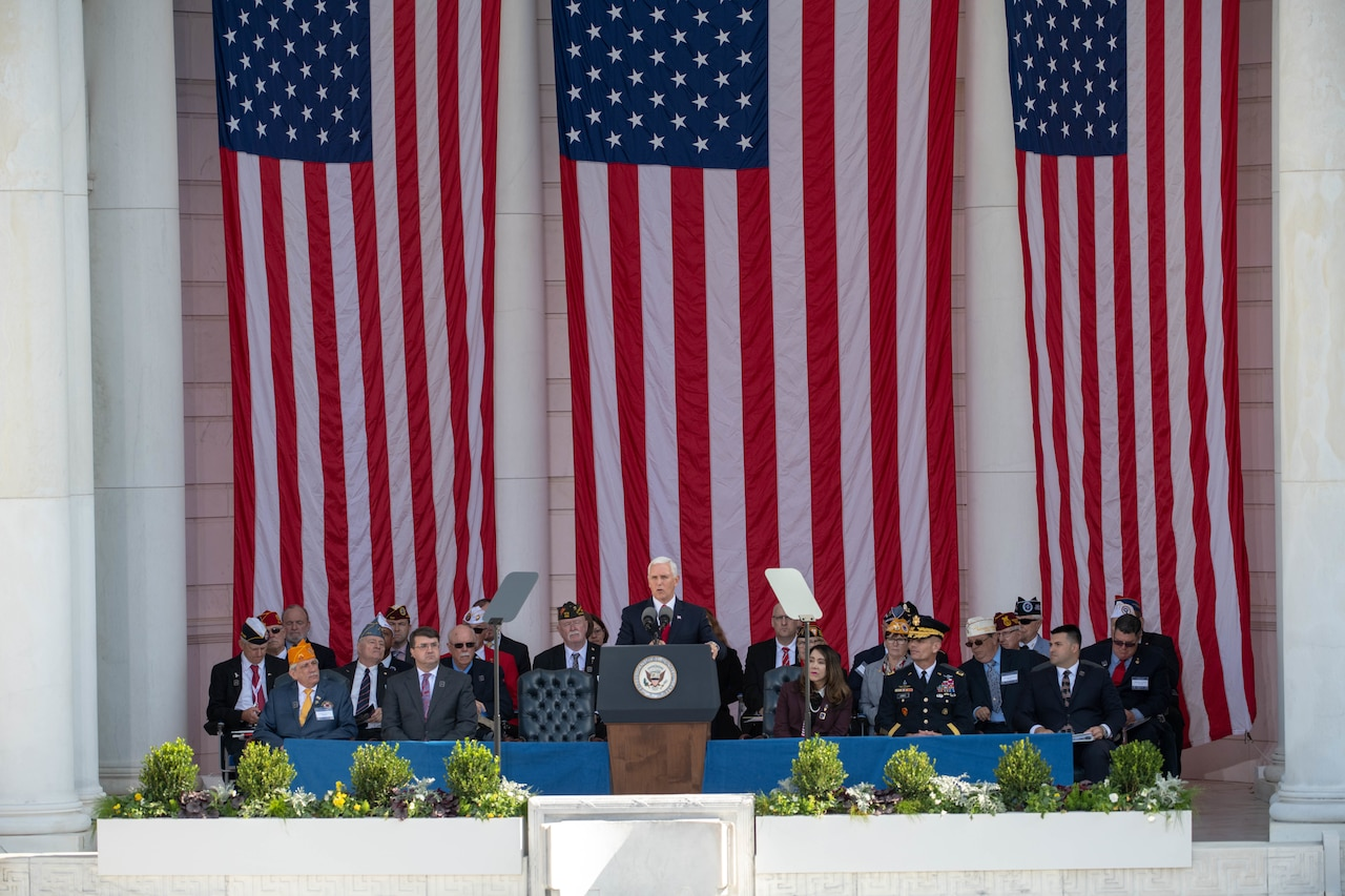 Vice President Mike Pence stands on stage with a group of people and three large American flags behind.