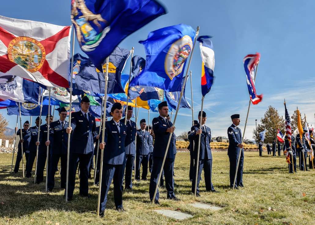 Photo of Airmen holding state flags during ceremony.