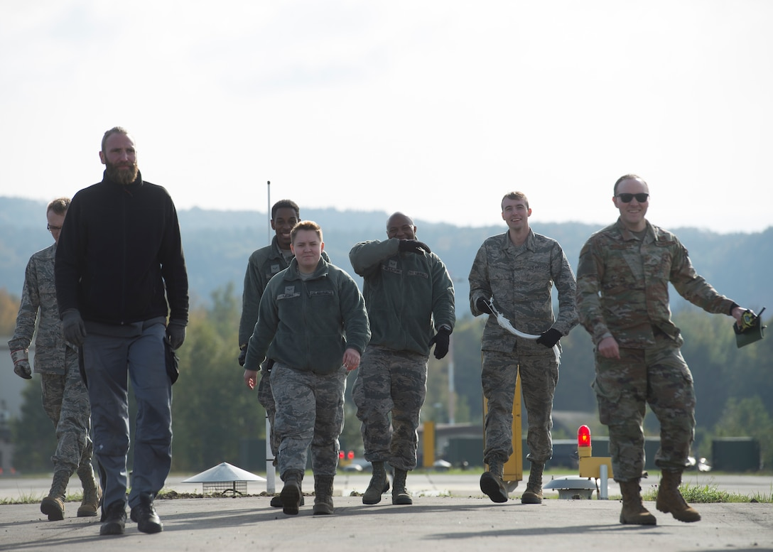 Members of the 786th Civil Engineer Squadron walk back to their cars after finishing runway maintenance at Ramstein Air Base, Germany, Oct. 28, 2019. Making sure the aircraft arresting system is ready at any moment is a daily job for power production technicians.