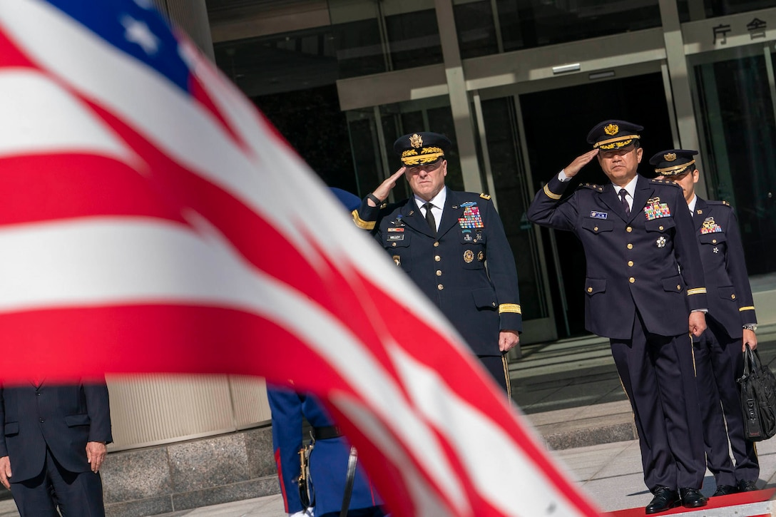 American and Japanese officers stand in the background saluting an American flag waving in the foreground.