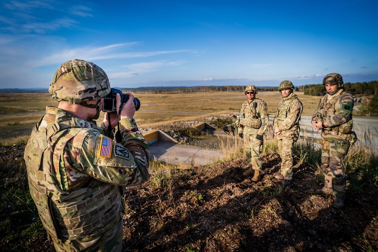 Pvt. 1st Class Stahlberg of 7th Army Training Command captures a photo of a U.S., French, and British Soldier at a tank live fire exercise during Dragoon Ready on Grafenwoehr Training Area.