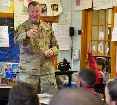 Army Col. Matthew Voyles, DLA Troop Support Medical supply chain director, talks with students during a Veterans Day event at the Gilbert Spruance Elementary School Nov. 7, 2019 in Philadelphia.