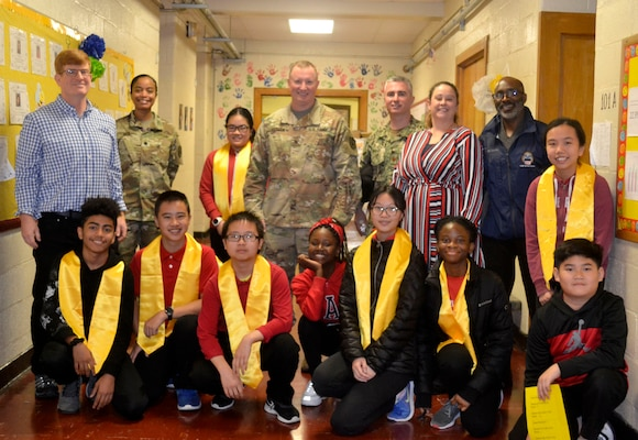 DLA Troop Support volunteers pose with students during a Veterans Day event at the Gilbert Spruance Elementary School Nov. 7, 2019 in Philadelphia.