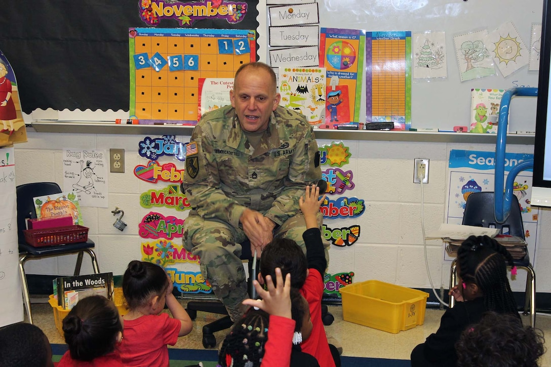 Army Sgt. 1st Class Richard Scaricaciottoli, a DLA Installation Philadelphia visual information specialist and Army reservist, speaks with students during a Veterans Day event at the Gilbert Spruance Elementary School Nov. 7, 2019 in Philadelphia.