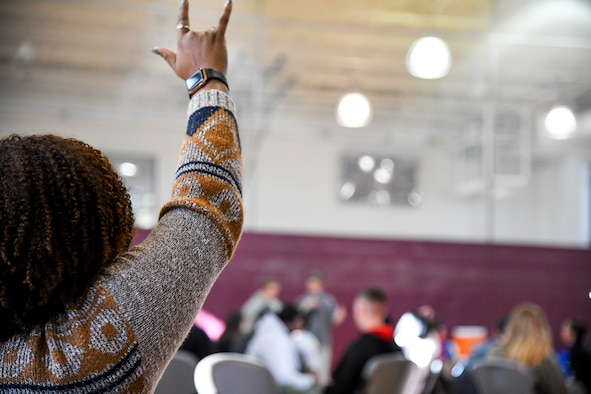 """A Challenge Day participant shows support for the person sharing their story by raising an """"I love you"""" sign Nov. 4, 2019 at Peterson Air Force Base, Colorado. Challenge Day helps people learn to recognize internal and external social and emotional issues and pressures. (U.S. Air Force Photo by Erica Blanton)"""