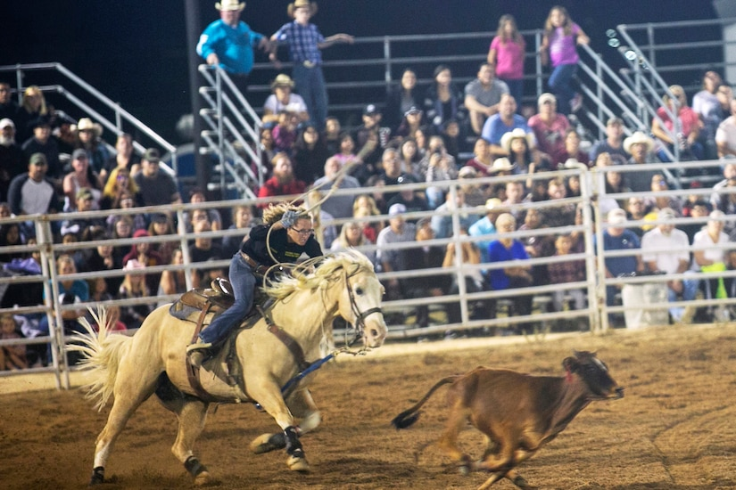 A rider is hunched over a horse as they chase a cow during a rodeo.
