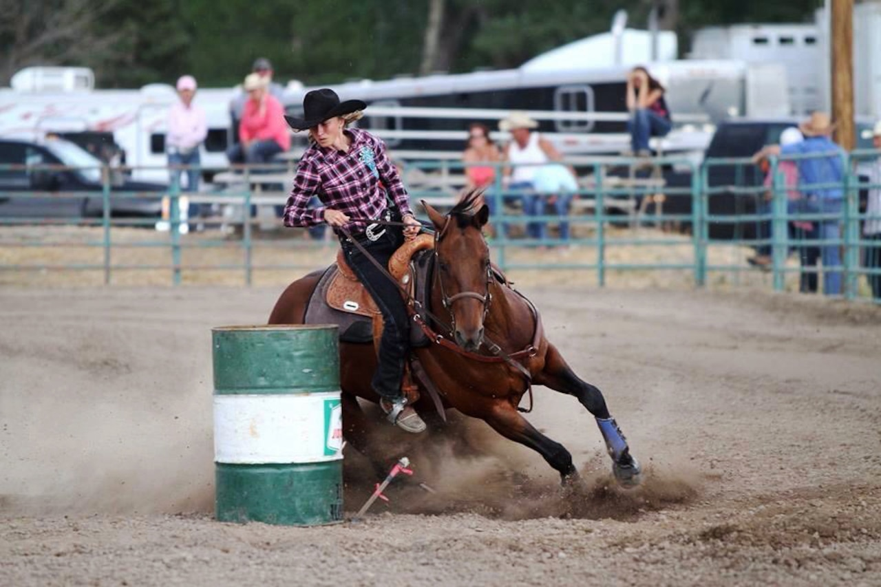 A rider steers a brown horse around a barrel during a rodeo.