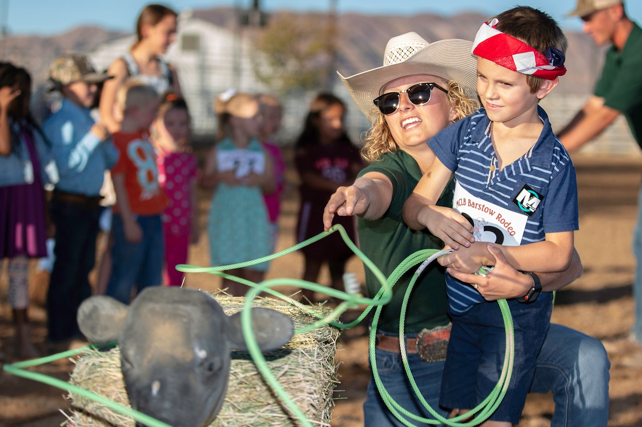 A woman wearing a white cowboy hat, shows a child wearing a red bandana how to rope a mock calf.
