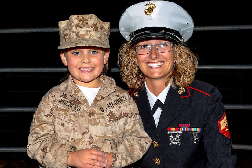 A Marine in a formal dress uniform smiles at the camera as she kneels down and has her arm around a young girl who is dressed up like a Marine.