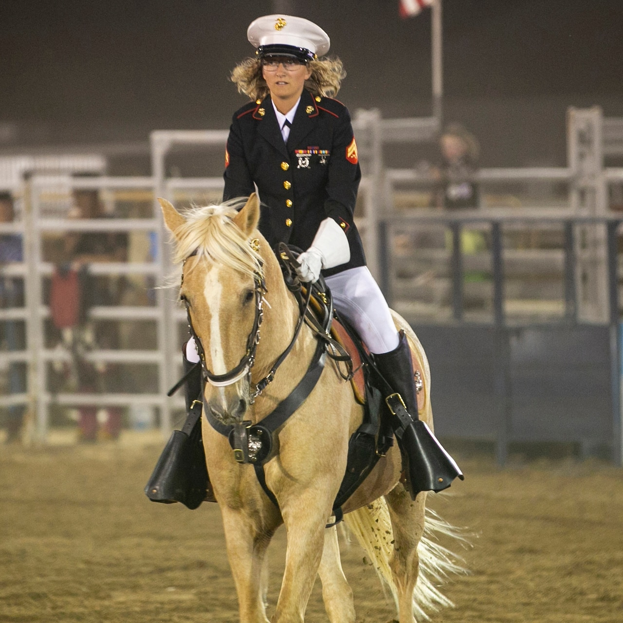 A Marine in formal dress rides a horse at a rodeo.