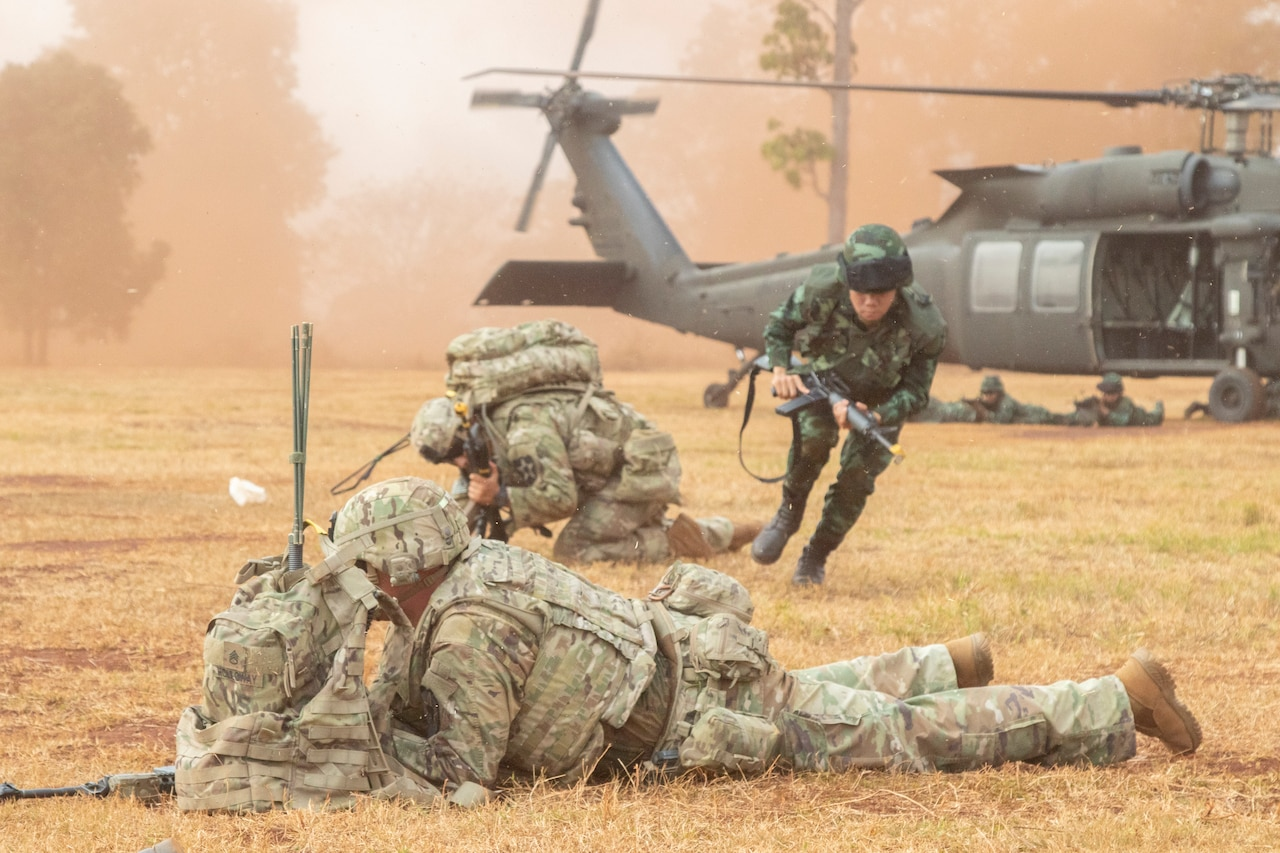 Thai soldier runs from a helicopter to join crouching U.S. soldiers during an air assault training mission.