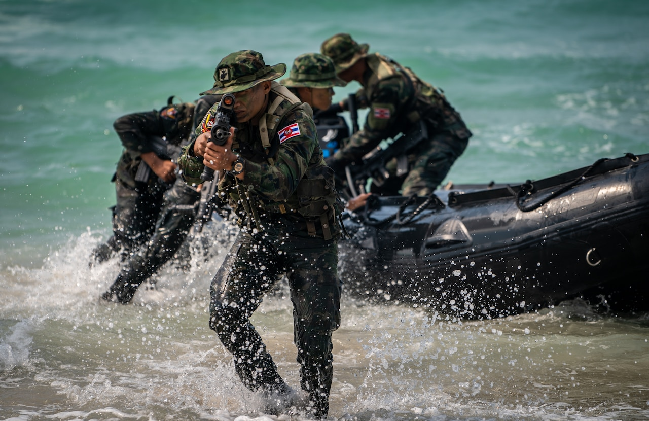 Thai Marines wade ashore from a rubber landing craft. The lead Marine aims a rifle.