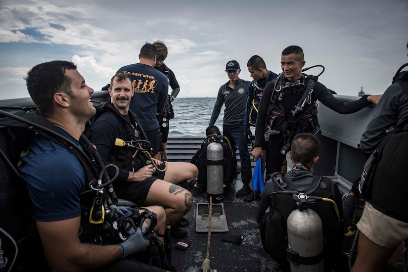 Sailors wearing diving gear talk on the deck of a boat.
