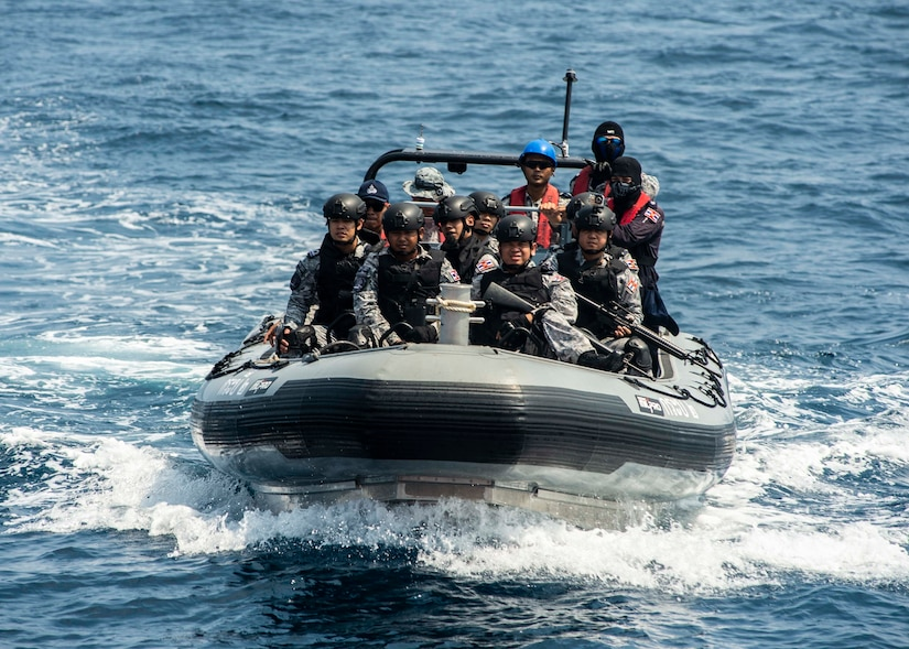 A small inflatable boat carries several sailors to a training vessel for a training exercise.