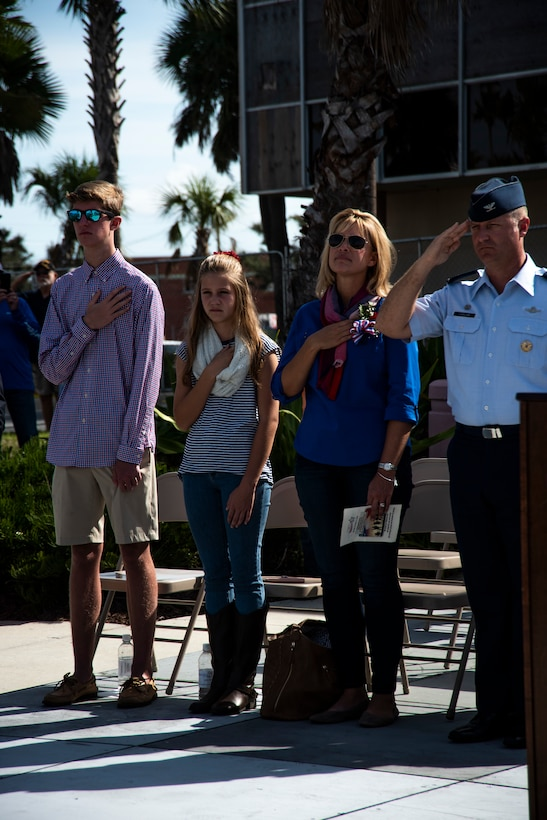 Col. Brian Laidlaw, 325th Fighter Wing commander, salutes the United States flag during the National Anthem and his family hold their hands over their hearts at the annual Veterans Day parade celebration and wreath laying ceremony on Nov. 11, 2019, at Panama City, Florida. The annual event celebrated those who served in the past and to honor the sacrifices made by the service member as well as their families, both at home and abroad. During the ceremony, Laidlaw highlighted the dedication families made as they supported their loved ones' service. Laidlaw identified that the military is a family business because families support the nation's defense as well. Laidlaw was accompanied by his wife Samantha, daughter Taylor and son Braden. (U.S. Air Force photo by Staff Sgt. Magen M. Reeves)