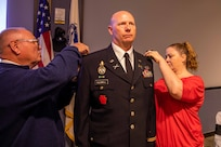 """U.S. Army Col. Christopher Caldwell has his new rank pinned on by his wife and father during his promotion ceremony at Joint Task Force Civil Support (JTF-CS) headquarters. The ceremony was presided over by JTF-CS Commanding General U.S. Army Maj. Gen. William """"Bill"""" Hall, and was attended by Caldwell's family, friends and fellow JTF-CS staff. (Official DoD photo by Mass Communication Specialist 3rd Class Michael Redd/RELEASED)"""
