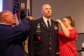"U.S. Army Col. Christopher Caldwell has his new rank pinned on by his wife and father during his promotion ceremony at Joint Task Force Civil Support (JTF-CS) headquarters. The ceremony was presided over by JTF-CS Commanding General U.S. Army Maj. Gen. William ""Bill"" Hall, and was attended by Caldwell's family, friends and fellow JTF-CS staff. (Official DoD photo by Mass Communication Specialist 3rd Class Michael Redd/RELEASED)"